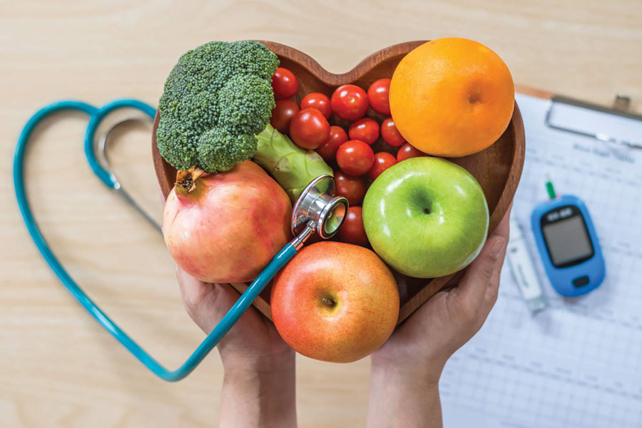 Two hands holding a bowl of fruit and vegetables with diabetes-related equipment in the background.