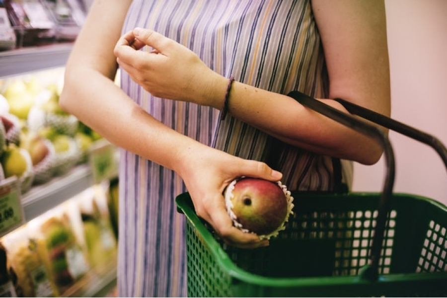 Woman puts apple in grocery basket