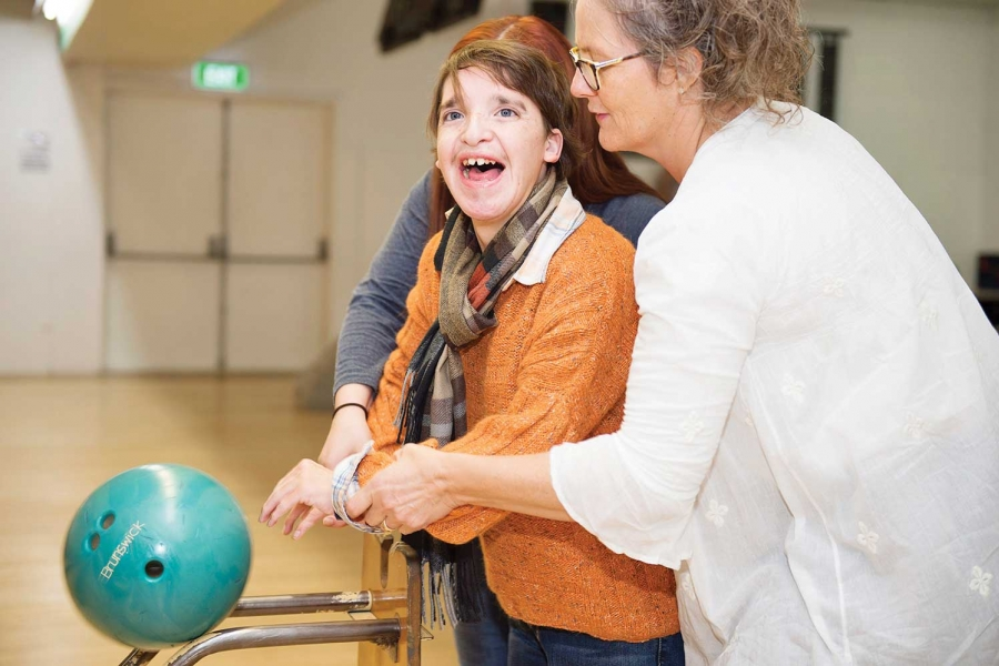 Teen with disability assisted at bowling centre.