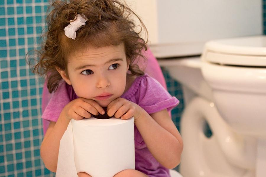 Girl resting cheek on toilet roll in toilet