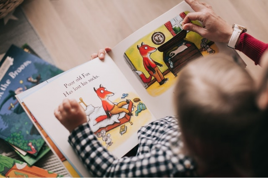 Child reading story book with adult