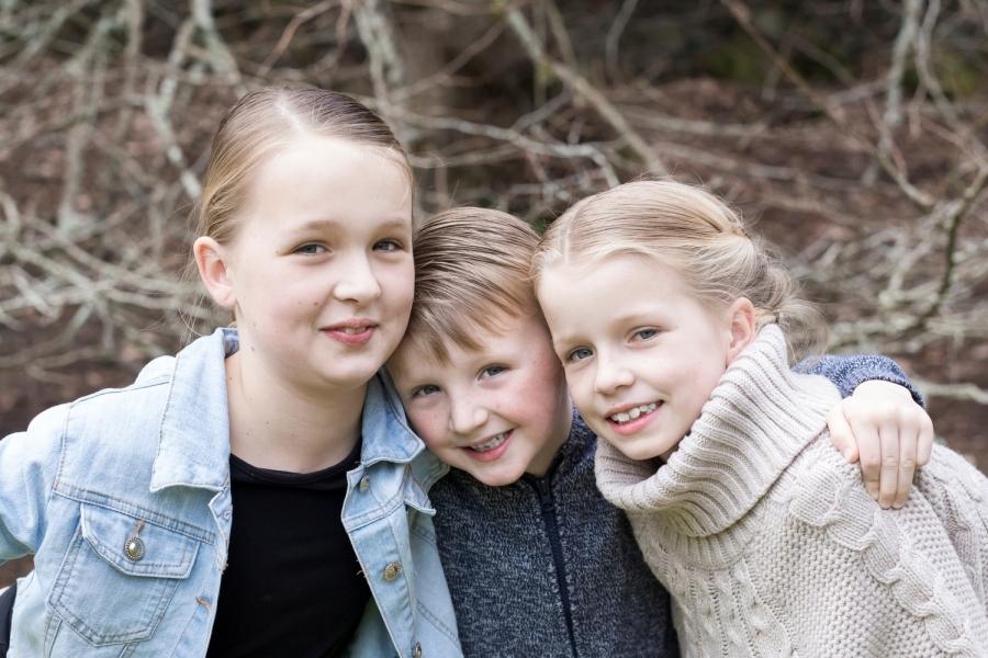 Three blonde children smiling