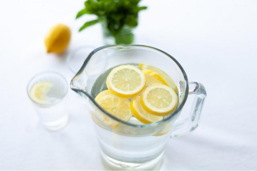 Sliced lemon in glass pitcher