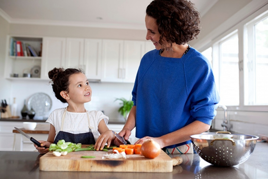 Mother and daughter chopping vegetables together