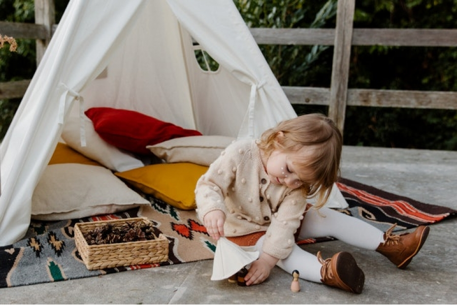Kid playing outside her tent on a picnic mat