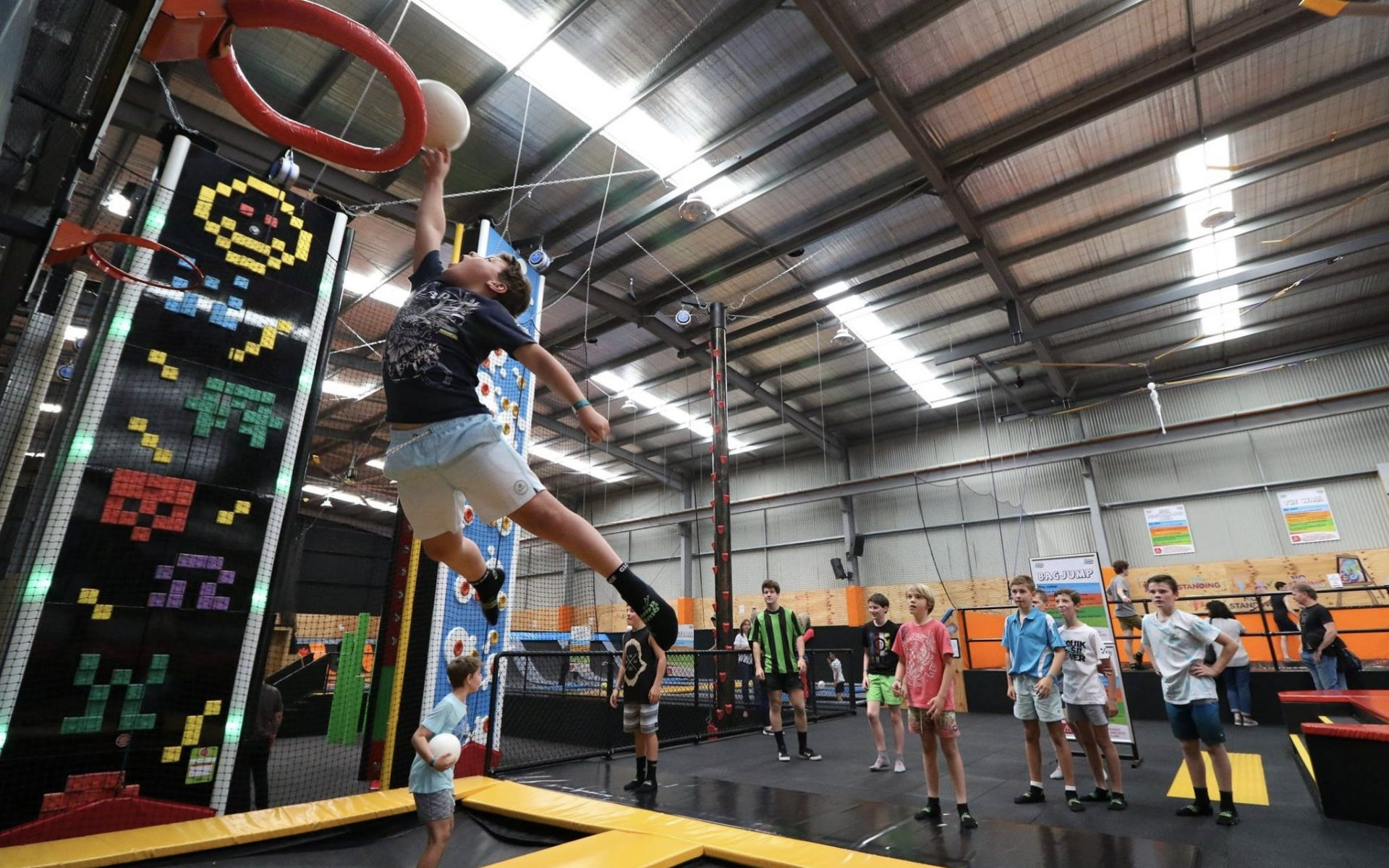 Image of children jumping on indoor trampolines and playing sports