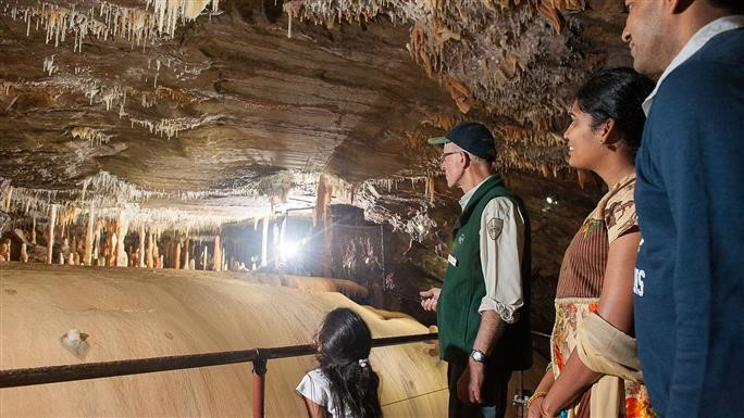 Image of a family of 3 with a tour guide exploring Buchan Caves