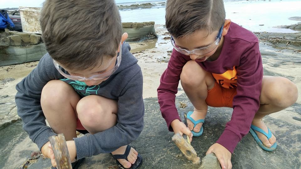 Image of two boys exploring on a rock with safety googles and hammers