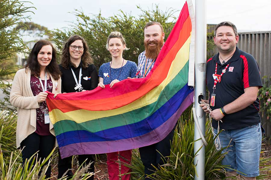 Members of the LGBTI Reference Group raising the rainbow flag for IDAHOBIT day