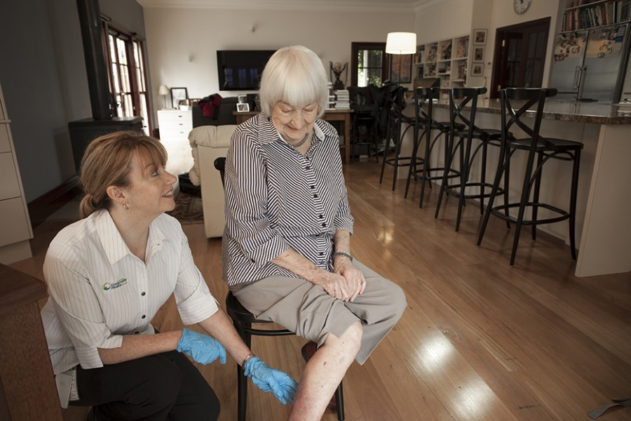 Nurse checking leg of elderly lady