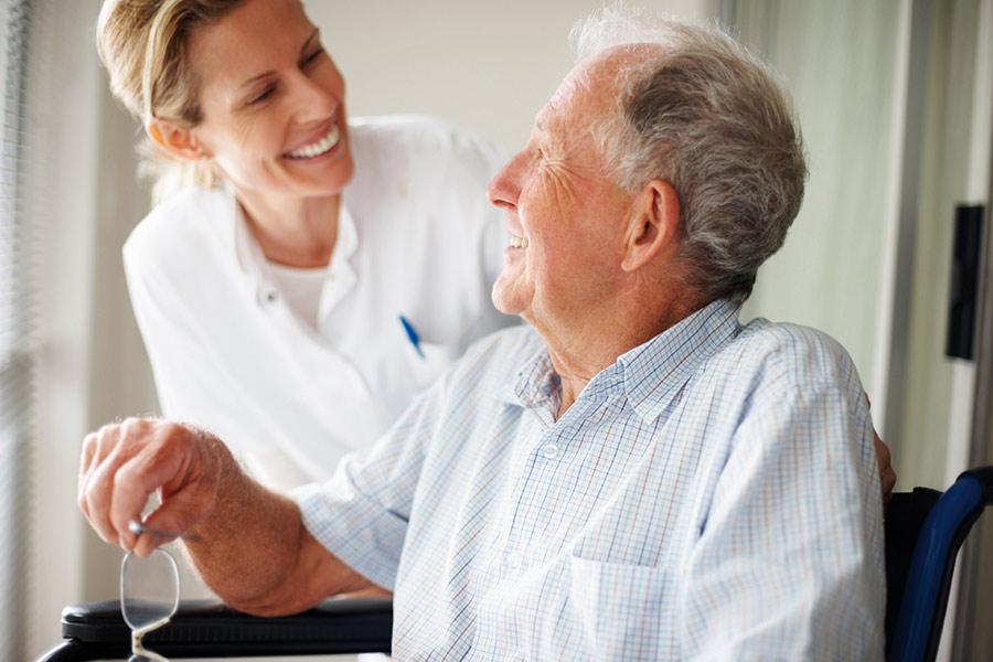 Nurse smiling at elderly on wheelchair