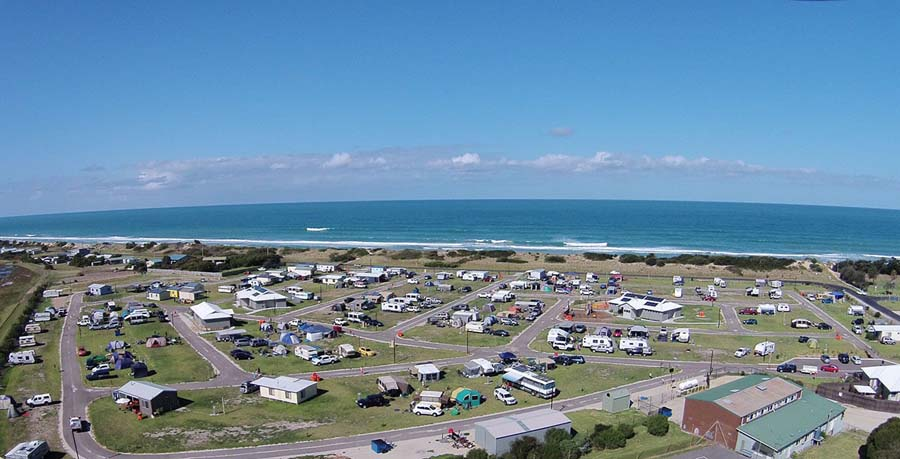 Image is an ariel view of the seaspray caravan park with view of the sea