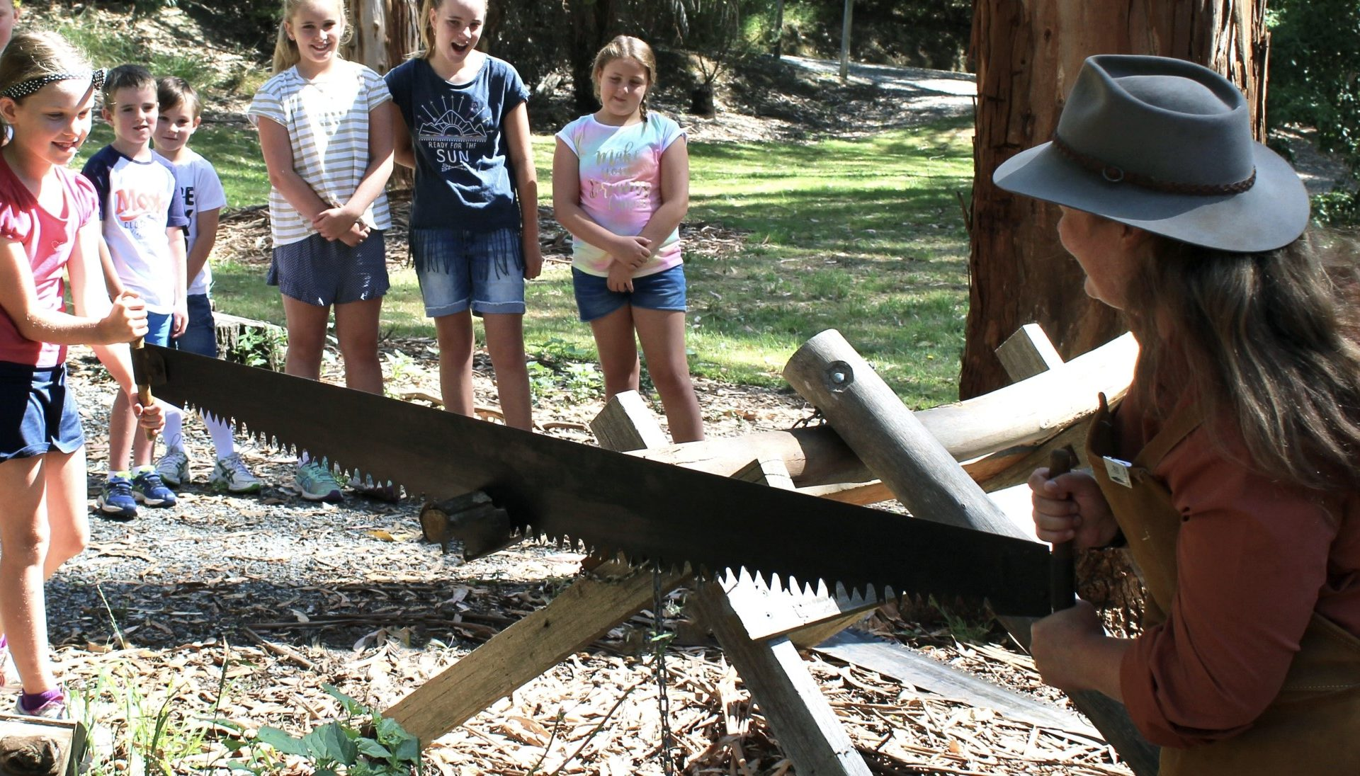 Image of a woman demonstrating an old saw while a group of young children watch