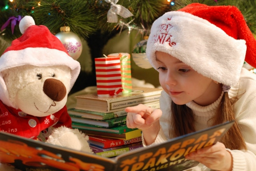 Kid reading to teddy during Christmas