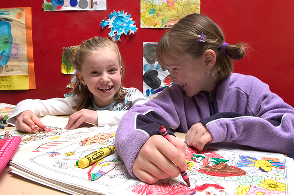 Two girls drawing and laughing