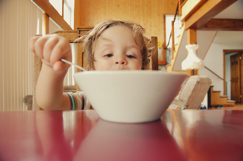 Toddler feeding himself from a large bowl
