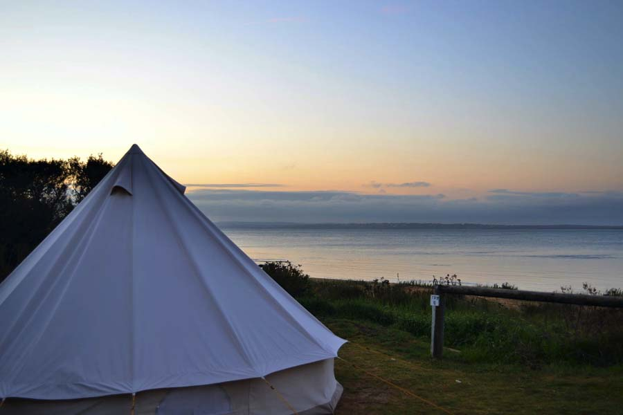 Image of glamping tent exterior over looking body of water at Phillip Island