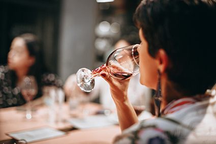 A women lifting a glass of wine to her lips to take a drink while out with friends
