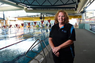 Woman stands next to a swimming pool.