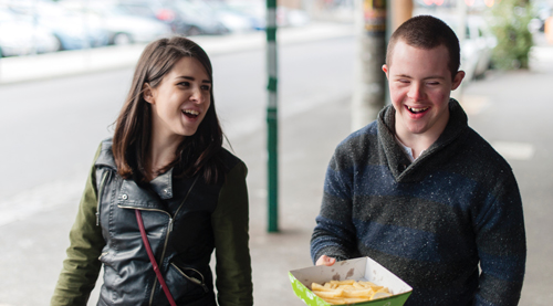 Girl and boy walk down street, laughing and eating hot chips.