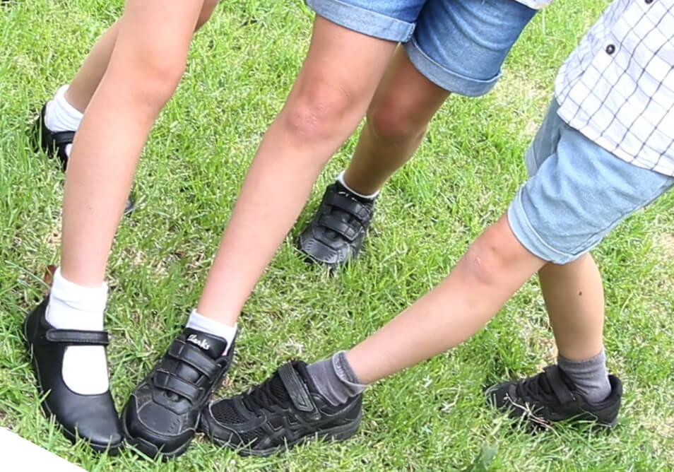 Legs of three children wearing fitted black school shoes