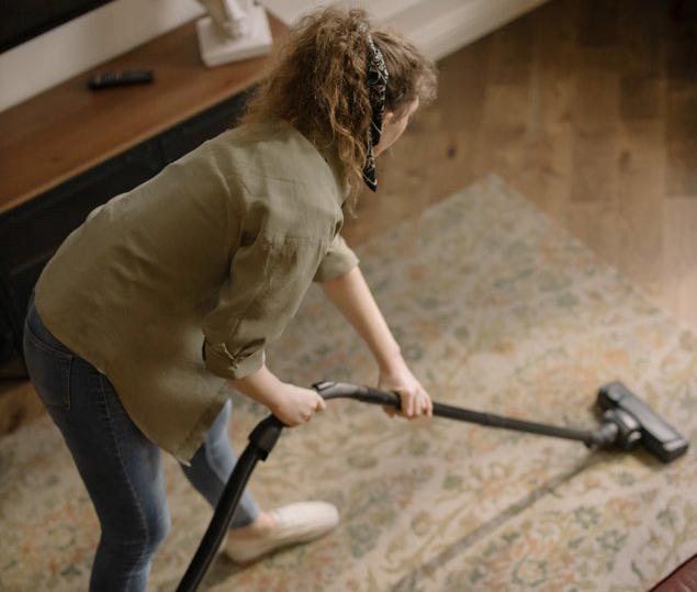 birds-eye view of a women vacuuming a rug