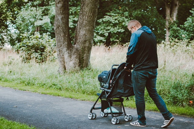 A father pushing his baby in a pram through a park surrounded by tall green grass and trees