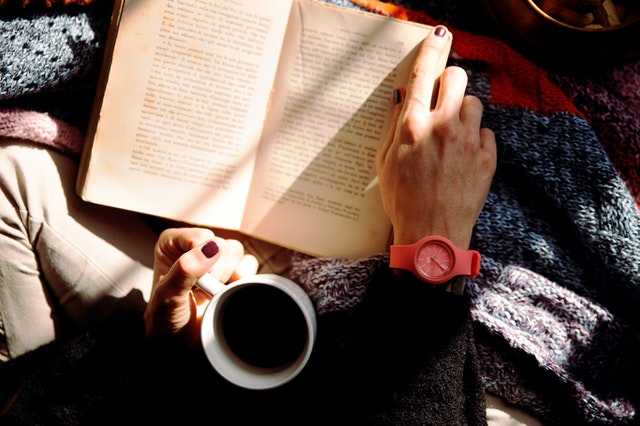 birds-eye view of a women reading book while holding a mug of black coffee