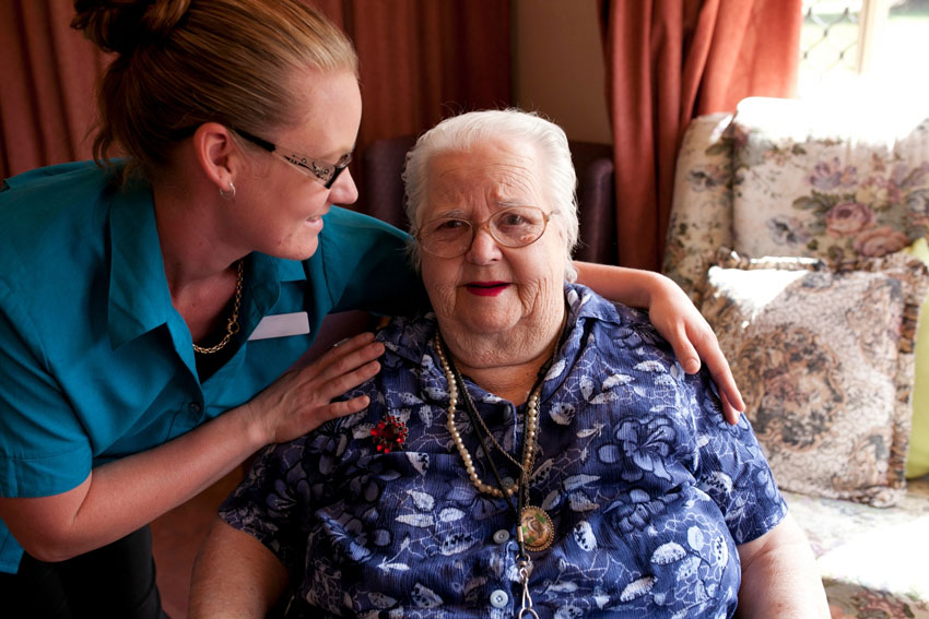 A nurse hugs the person she is caring for.