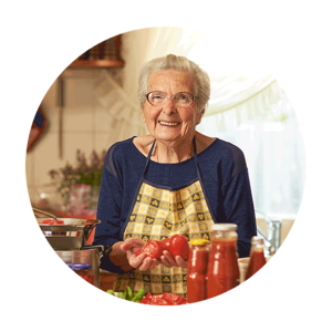 A senior women wearing glasses and and apron holds chopped tomatoes while smiling at the camera