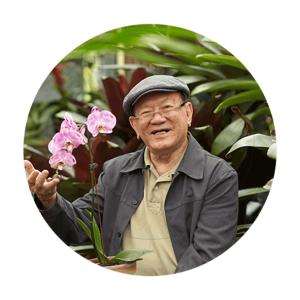 A senior man sits in a garden and holds a pink blooming orchid. He is wearing a hat and glasses and smiles at the camera