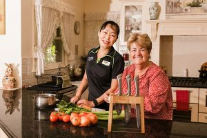 A senior women chopping vegetables. She is pictured with an LCHS staff member. Both are smiling at the camera.